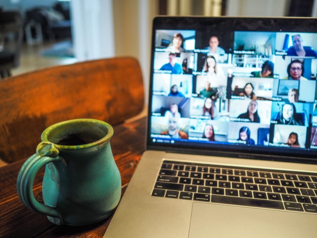 A laptop sitting on a wooden table, with a virtual meeting on the screen. There are a lot of attendees with their cameras on, and there is a coffee mug next to the laptop.